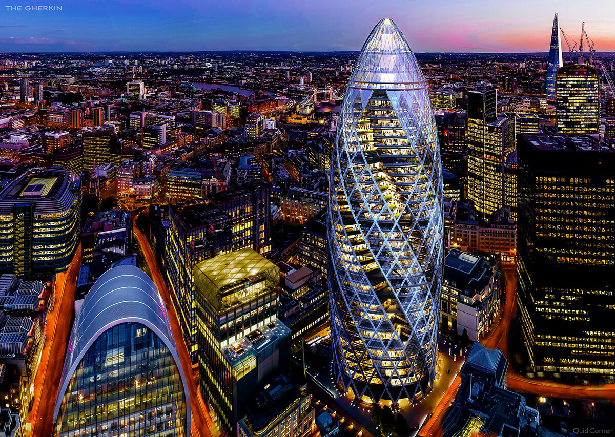 Nighttime aerial view of the gherkin building in London, a tall cylindrical building